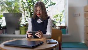La mujer joven mira noticias en el smartphone para el desarrollo de su negocio almacen de video