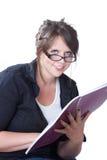 La mujer joven mira para arriba de su planificador Imagen de archivo