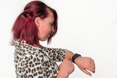 La mujer joven mira su nuevo reloj digital Fotos de archivo libres de regalías