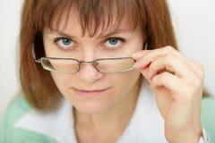 La mujer joven mira terminantemente sobre gafas Foto de archivo libre de regalías