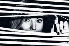La mujer joven mira a través de la persiana foto de archivo libre de regalías