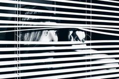 La mujer joven mira a través de la persiana imagen de archivo
