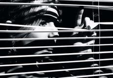 La mujer joven mira a través de la persiana imagenes de archivo