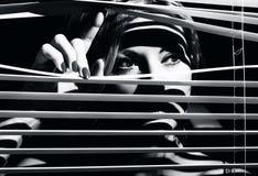 La mujer joven mira a través de la persiana imagen de archivo libre de regalías