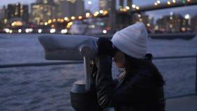 La mujer joven mira a través de un catalejo el puente de Brooklyn Nueva York metrajes