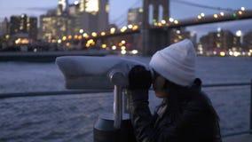 La mujer joven mira a través de un catalejo el puente de Brooklyn Nueva York almacen de video