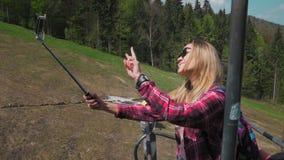 La mujer joven monta en la elevación de la montaña, hace el selfie usando smartphone y Selfiestick fondo del bosque adentro almacen de metraje de vídeo