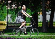 La mujer joven monta la bicicleta en el parque Fotografía de archivo