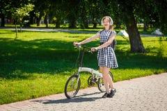 La mujer joven monta la bicicleta en el parque Imagenes de archivo