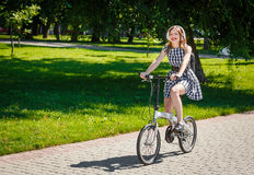 La mujer joven monta la bicicleta en el parque Foto de archivo libre de regalías