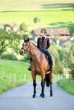 La mujer joven monta un caballo en verano Foto de archivo libre de regalías