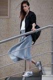La mujer joven morena en estilo sport camina abajo de las escaleras Imagenes de archivo