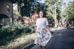 La mujer joven morena sensual hermosa en la blusa blanca y la falda con las flores caminan en la calle cerca del arbusto de rosas foto de archivo libre de regalías