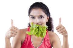 La mujer joven muerde las hojas de la espinaca Foto de archivo