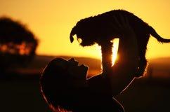 La mujer joven muestra alegría y felicidad cuando el perro de perrito perdido encontró la caja fuerte Foto de archivo libre de regalías
