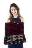La mujer joven muestra el clarinete en caso abierto con la guarnición del terciopelo Foto de archivo libre de regalías