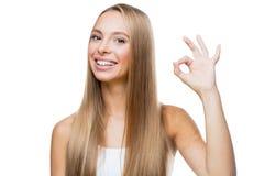 La mujer joven muestra la autorización del gesto en el fondo blanco Fotos de archivo libres de regalías