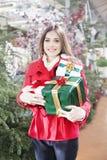 La mujer joven muestra sus paquetes del regalo dentro de una tienda de la Navidad foto de archivo