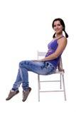 La mujer joven muy hermosa con las colas arroja sentarse en una silla de lado aislada en el fondo blanco Imagen de archivo libre de regalías