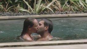 La mujer joven nada al hombre en la piscina y lo besa metrajes