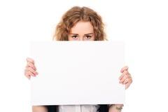 La mujer joven observa sobre una exhibición promocional en blanco aislada en a Imagenes de archivo
