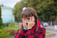 La mujer joven oculta su cara en sus palmas y espías imagen de archivo libre de regalías