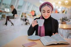 La mujer joven ocupada del arabain leyó el libro y el café de la bebida Ella él imagen de torneado Ella se sienta en lado La muje foto de archivo