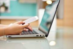 La mujer joven ocupada está mecanografiando en el ordenador portátil y está utilizando p móvil Foto de archivo
