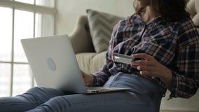 La mujer joven paga compras con la tarjeta de banco mientras que se sienta en el apartamento almacen de video