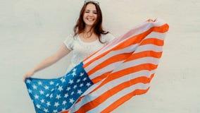 La mujer joven patriótica atractiva sostiene la bandera americana antes de su cuerpo mientras que baila delante de la pared que c almacen de metraje de vídeo