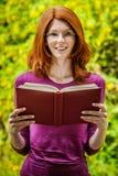 La mujer joven pelirroja lee el libro Foto de archivo libre de regalías