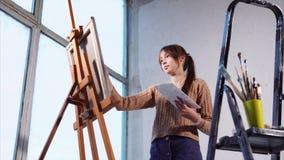 La mujer joven pinta las pinturas de aceite en lona en espacio del arte con las ventanas grandes almacen de metraje de vídeo