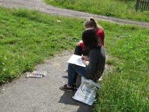 La mujer joven pinta una imagen bajo la orientación de su profesor Fotografía de archivo libre de regalías