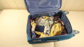 La mujer joven pone boletos en la maleta y cierra la cremallera 2 tiros almacen de metraje de vídeo