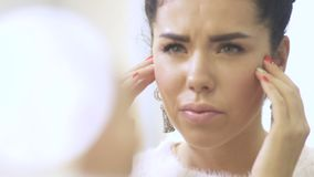 La mujer joven pone el ` t como su piel de la cara almacen de metraje de vídeo