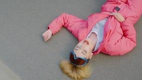 La mujer joven pone en la carretera de asfalto almacen de video