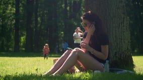 La mujer joven pone en los auriculares inalámbricos del auricular almacen de video