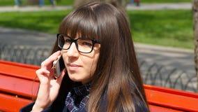 La mujer joven pone los vidrios y hablar en el teléfono modile en un parque de la ciudad Muchacha que asiste en un banco rojo al  metrajes
