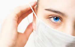 La mujer joven pone una máscara protectora para proteger contra el virus foto de archivo