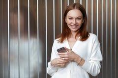 La mujer joven positiva con apelar mirada, ha satisfecho la expresión facial, vestida en la ropa blanca, lee el artículo en págin fotos de archivo libres de regalías