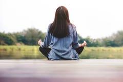 La mujer joven practica yoga en al aire libre El sentarse en la posición de loto Concepto de la vida desenchufada y de la salud m fotografía de archivo