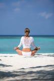 La mujer joven practica yoga y medita en la posición de loto respecto a la playa Fotos de archivo libres de regalías