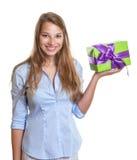 La mujer joven presenta un regalo de la Navidad Foto de archivo