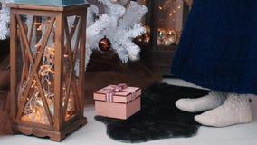 La mujer joven puso los regalos debajo del árbol de navidad Concepto de la celebración de la Navidad metrajes