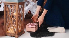 La mujer joven puso los regalos debajo del árbol de navidad Concepto de la celebración de la Navidad almacen de video