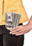 La mujer joven puso un billete de dólar en el bolsillo Foto de archivo libre de regalías