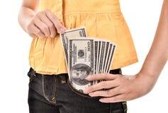 La mujer joven puso un billete de dólar en el bolsillo, aislado en b blanco Fotografía de archivo