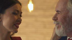 La mujer joven que alimenta al viejo hombre, ligando con él, ama a pesar de diferencia de la edad almacen de metraje de vídeo