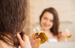 La mujer joven que aplica la máscara del aceite al pelo inclina Fotografía de archivo libre de regalías
