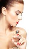 La mujer joven que aplicaba perfume en sí misma aisló en el backgr blanco Imagenes de archivo